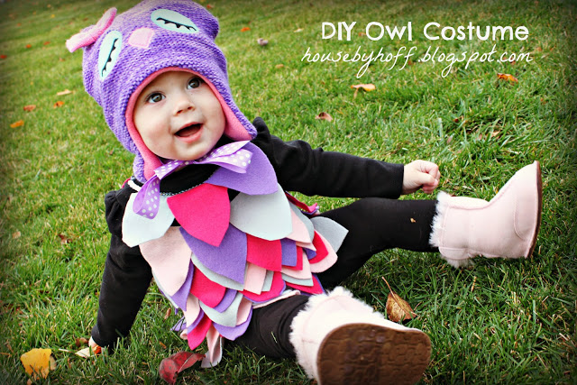 Little girl sitting i grass in owl costume