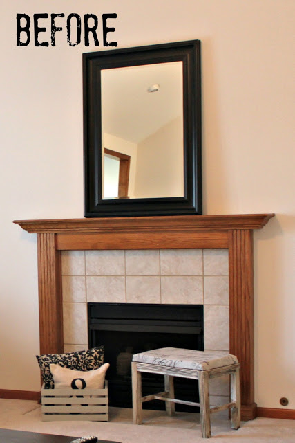 A tiled fireplace with a wooden mantel and a mirror above it.