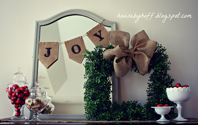 A mirror with a banner that says joy.    The boxwood wreath with a burlap bow and jars filled with candies on the mantel.