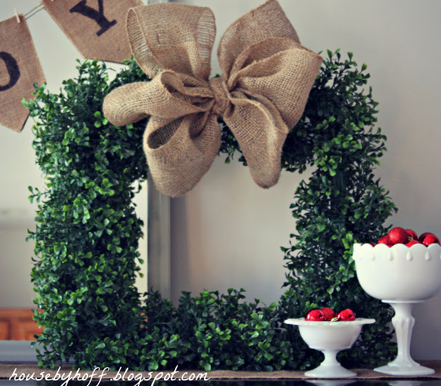 Green boxwood wreath with a burlap bow on the mantel.