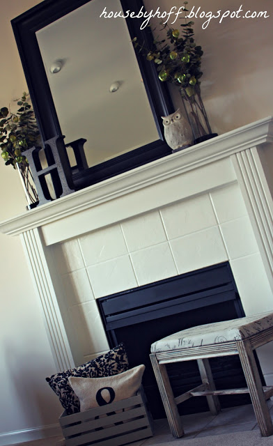 The same fireplace but painted a white color with the mantel painted as well.    A black mirror is on the mantel and a foot stool is in front of the fireplace.