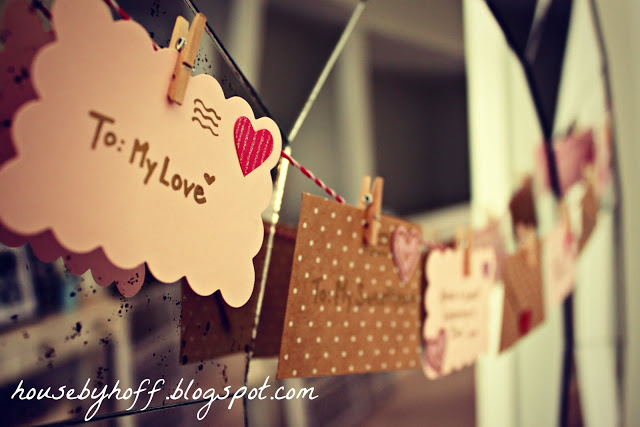 Love envelopes hanging as a garland by clothespins.