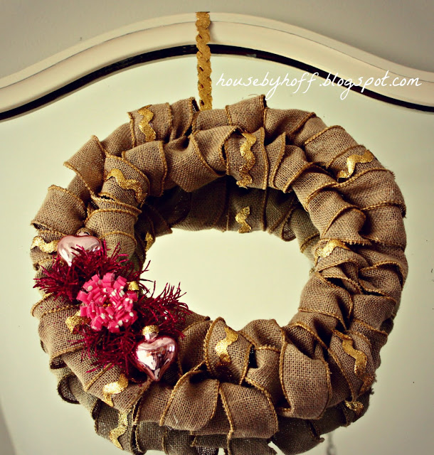 A burlap wreath hanging in front of a mirror.