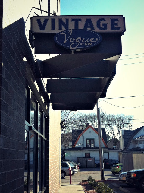 A sign outside a store that says Vintage Vogue Goodwill.