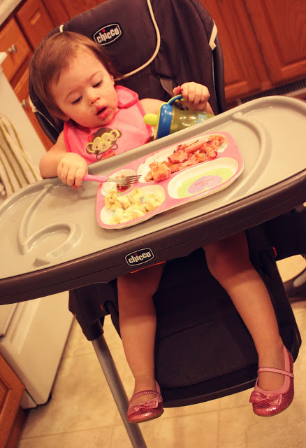 Little girl eating her breakfast at her high chair.