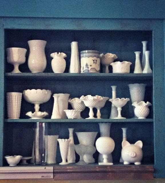 A shelf containing all different sizes and types of white pottery.