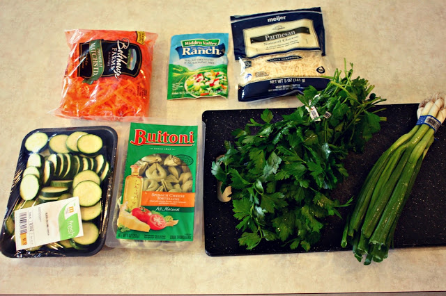 Carrot, cucumber, parmesan, tortellini, chives on counter.