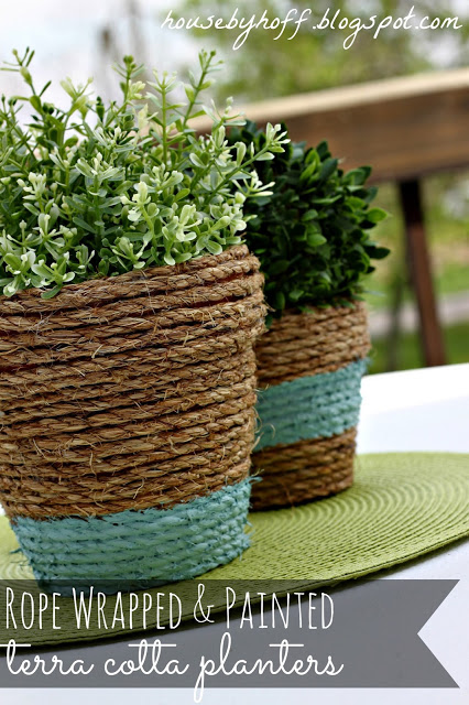 Terra cotta pots with decorative rope wrapped around and green plants in them.