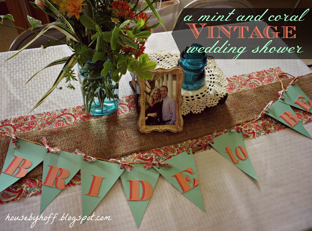 Table with bride to be banner on front in mint and coral.