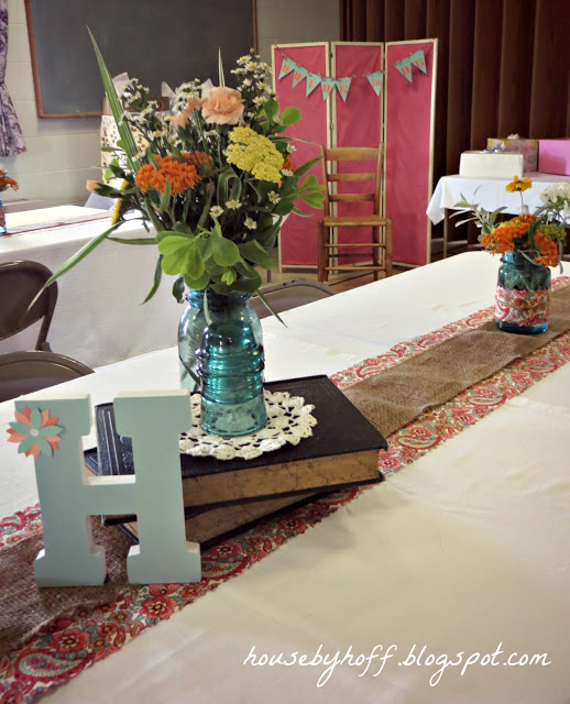 Flowers in a vase on vintage books on table.