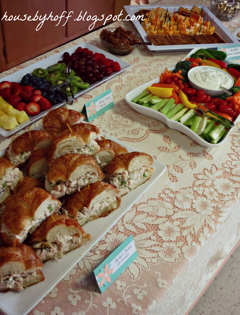Table of food with sandwiches and fruit and vegetable tray.