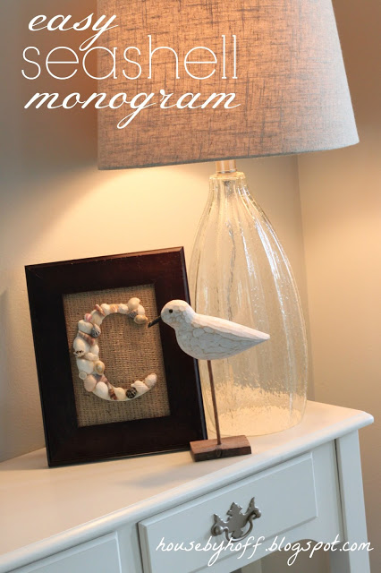 Seashell monogram in a frame on a desk.