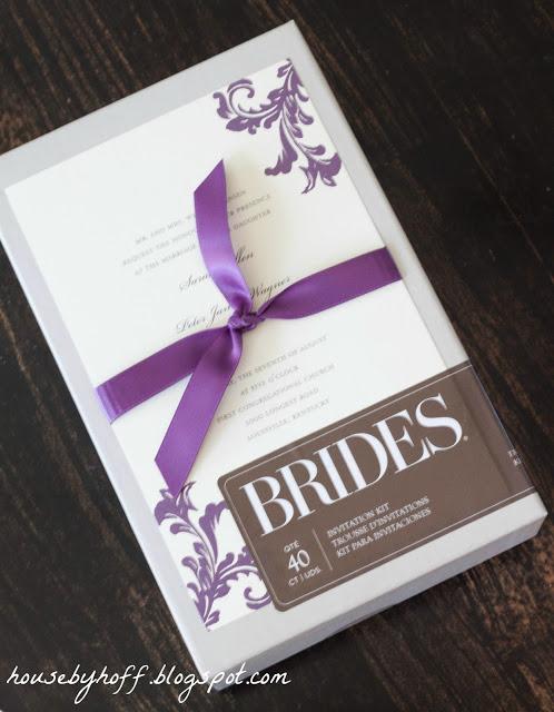 The invitation with a purple ribbon.