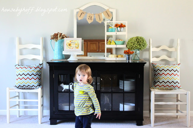 Little girl standing in front of the china cabinet and fall vignette.