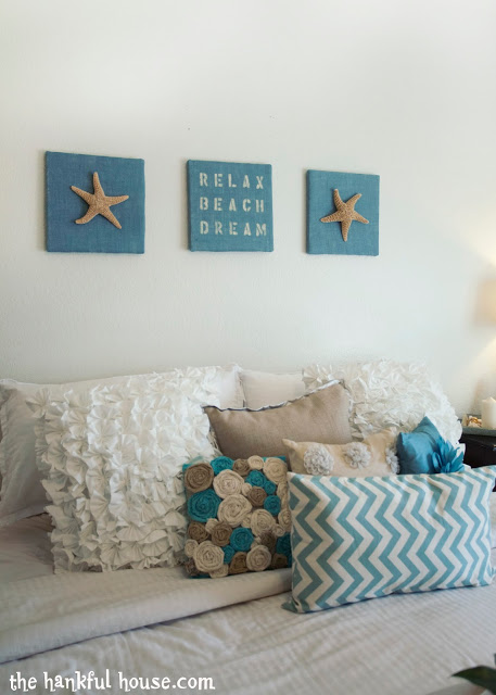 Bedroom with beachy pictures above the bed.