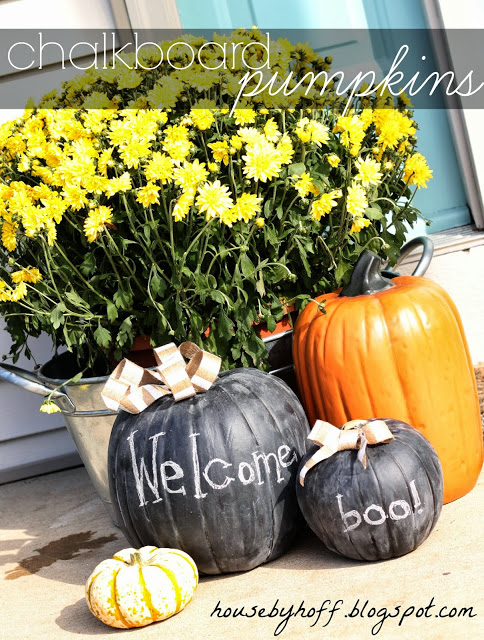 Fake pumpkins spray painted with welcome and boo on the front porch.