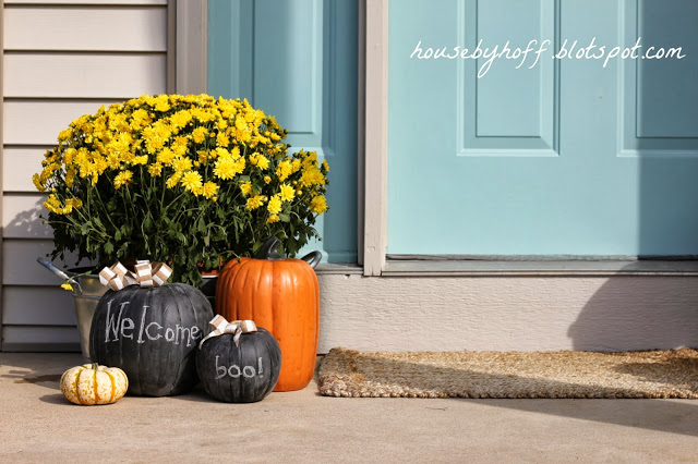 Front porch with light blue door, yellow flowers in a planter, and fake pumpkins.