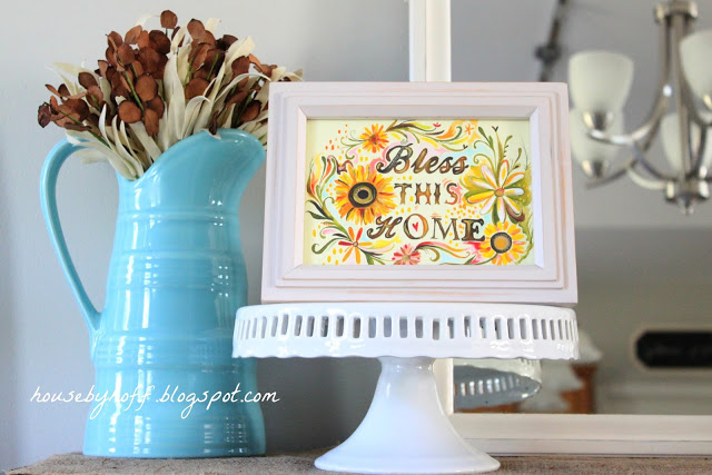 Bless this home sign on a white cake stand on the mantel.