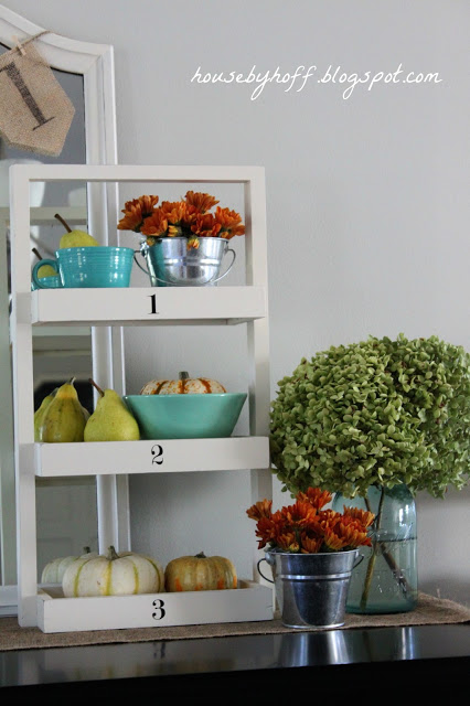 White shelf with flowers, and pumpkins on it.