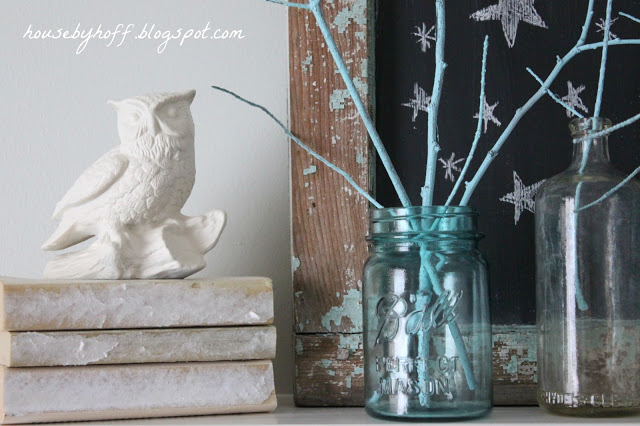 White owl figure sitting on antique books beside the glass mason jars on mantel.