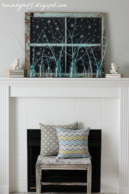 White fireplace mantel with bench in front and pillows on bench.