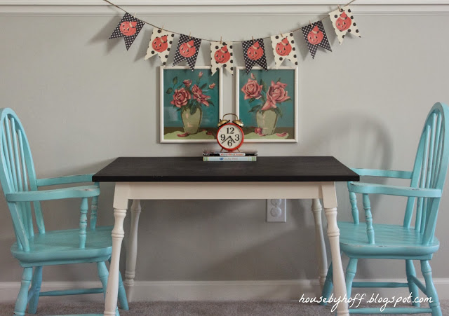 A table with blue chairs, and a pumpkin garland on the wall.