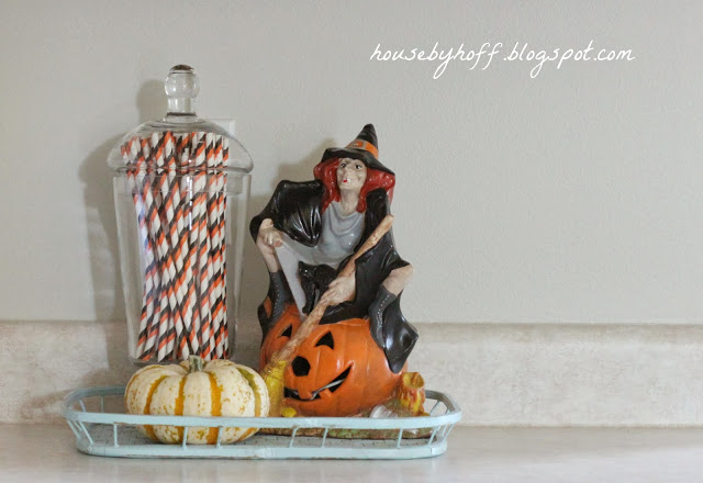 A witch sitting on a jack-o-lantern beside orange and black straws on the counter.
