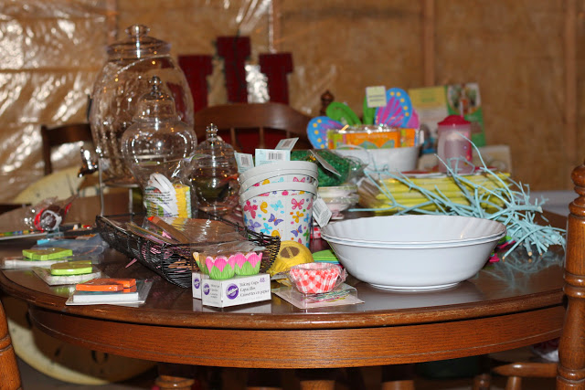 Wooden table filled with party planning items, paper cups, bowls, cupcake holders.