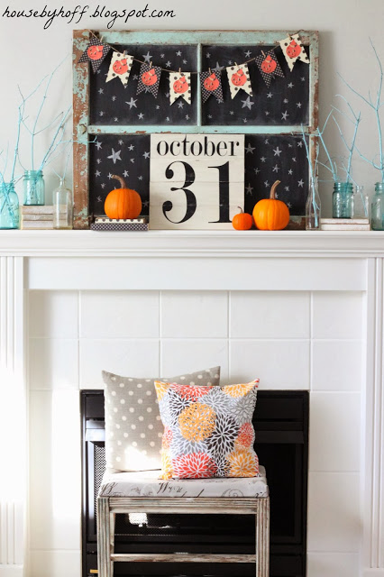 A white fireplace mantel decorated for Halloween.