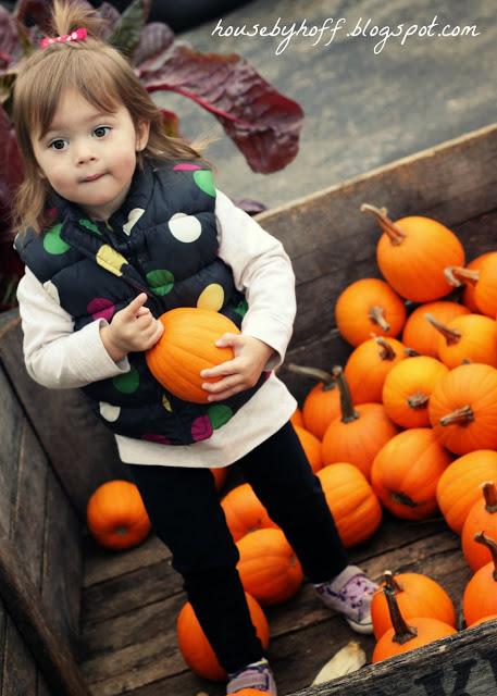 Little girl carrying a pumpkin.