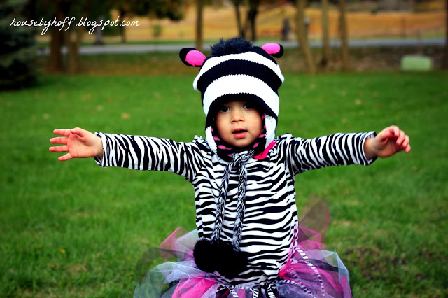 Zebra costume girl with arms out for a hug.
