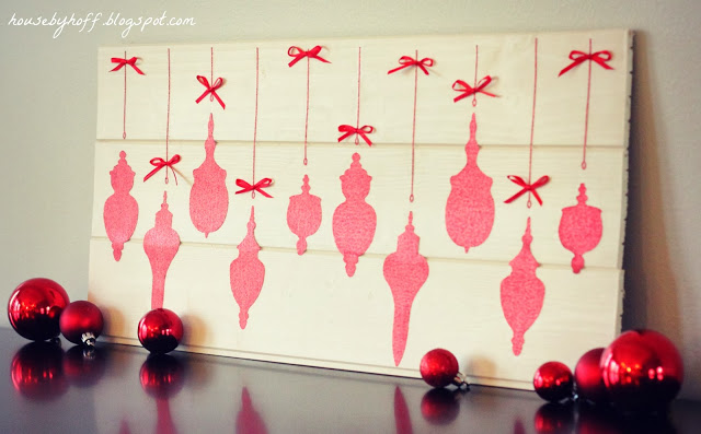 Sparkly ornament cut outs on a board with red bows.