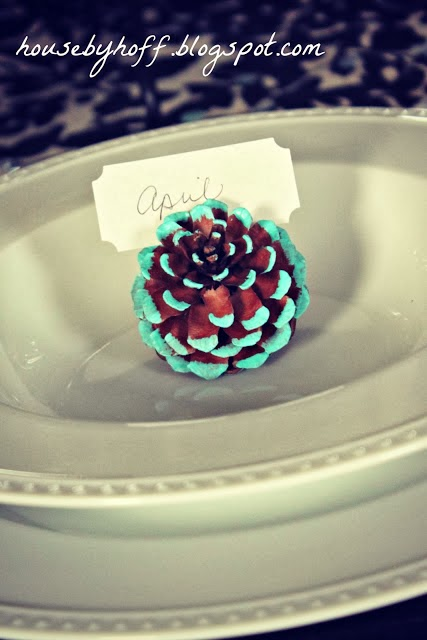The pine cone with tips painted blue and on the table as a card holder.