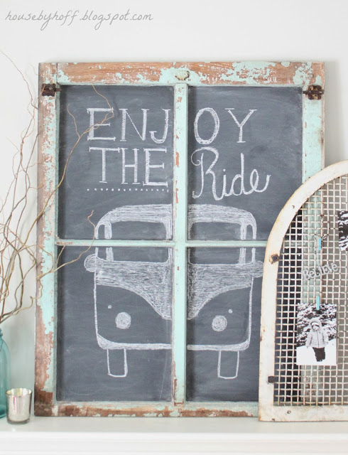 A chalkboard on the mantel with a drawn VW bus saying enjoy the ride.