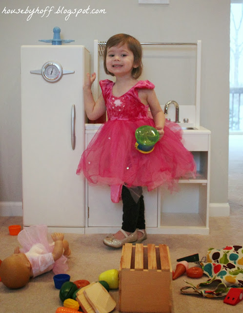 A little girl in a pink tutu dress waving in her playroom.