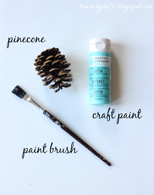 A paint brush, pine cone, and paint.