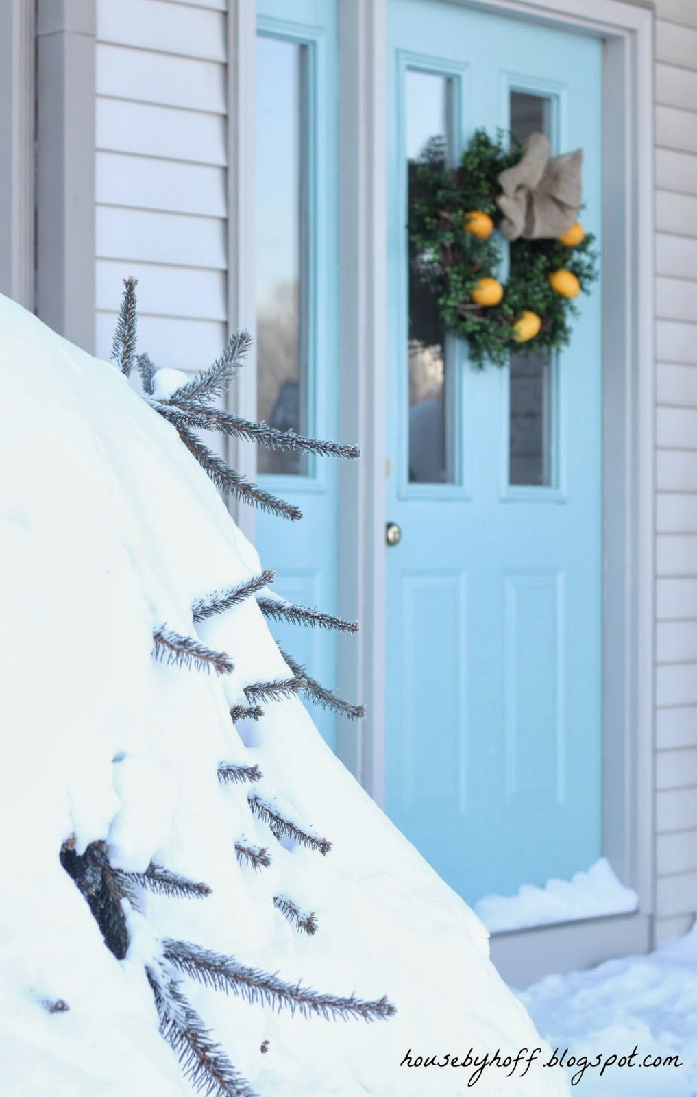 A side angle of the wreath on the door with snow on the porch.