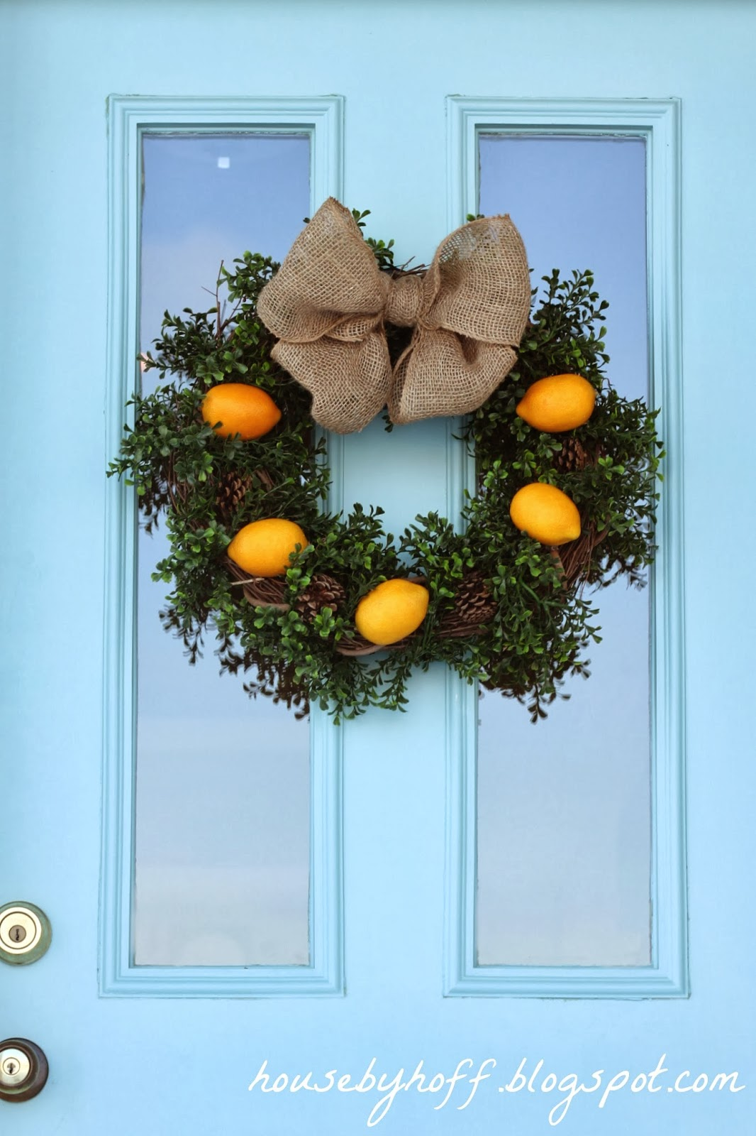 A blue door with the lemon wreath hanging on it.