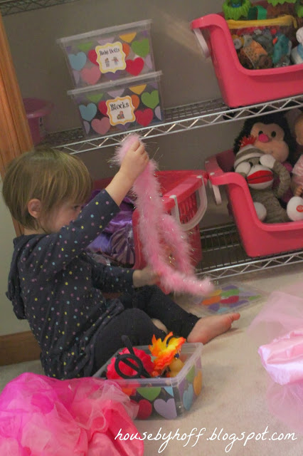 Little girl playing with pink fluffy feather boa.