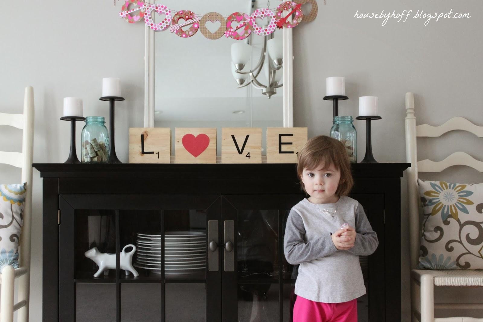 Little girl posing in front of the Love art.