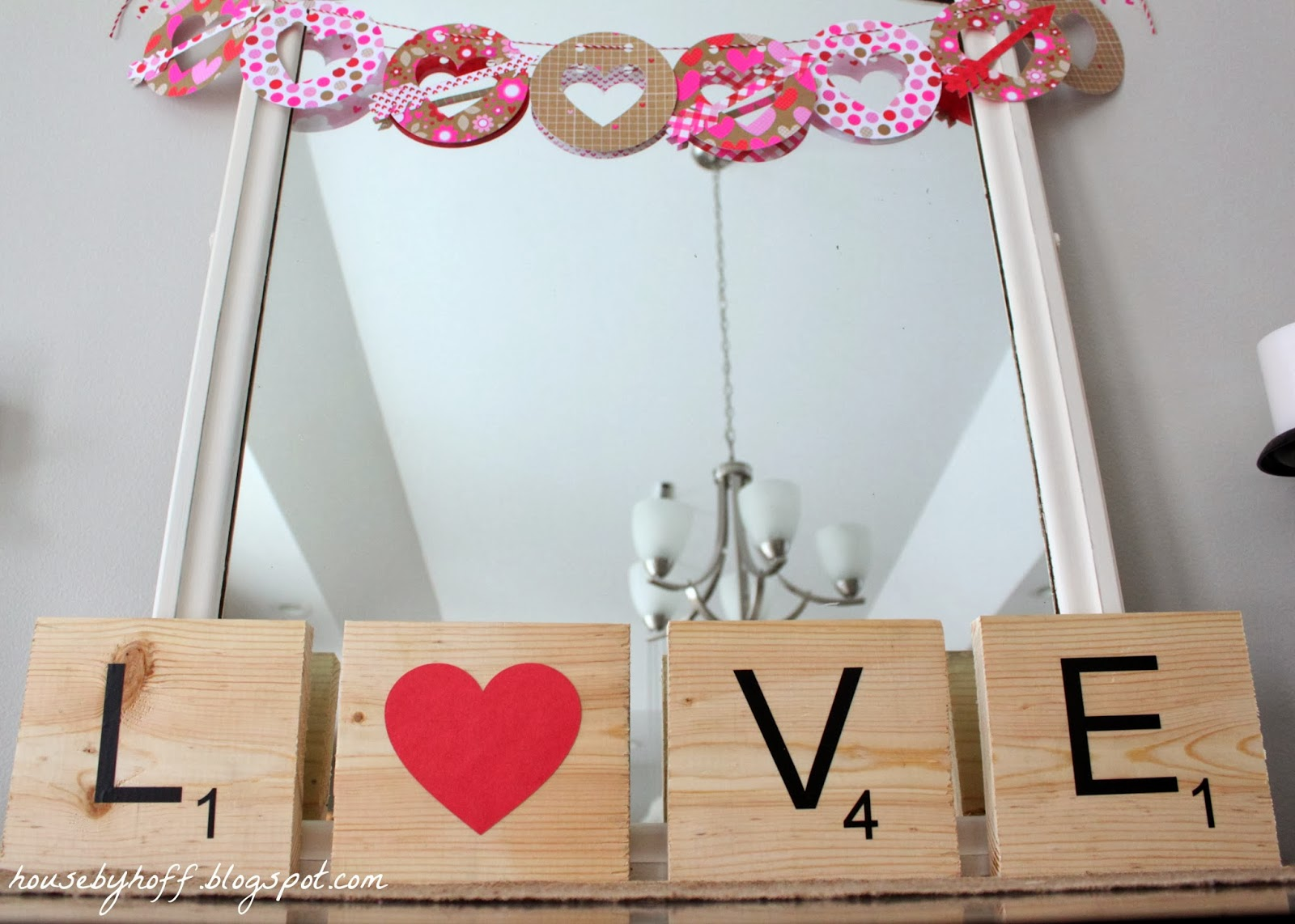 A scrabble love sign displayed in front f a mirror.