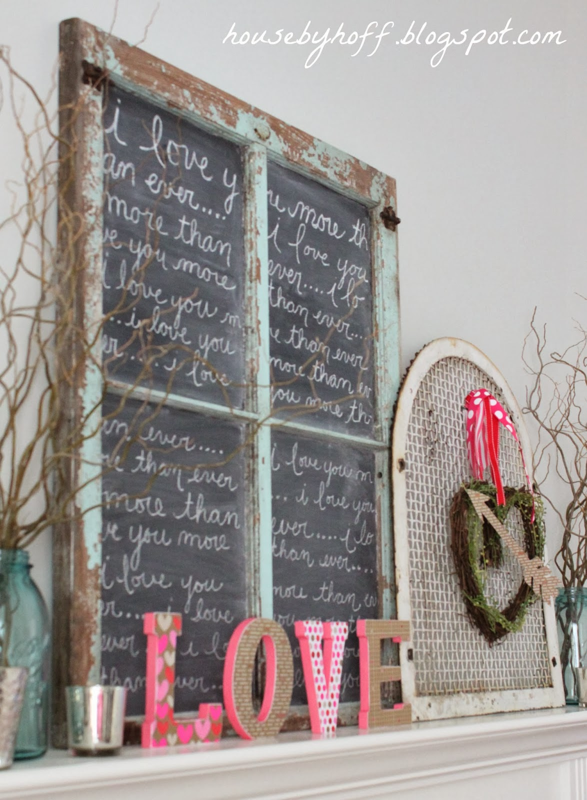A love sign on the mantel beside the wreath.