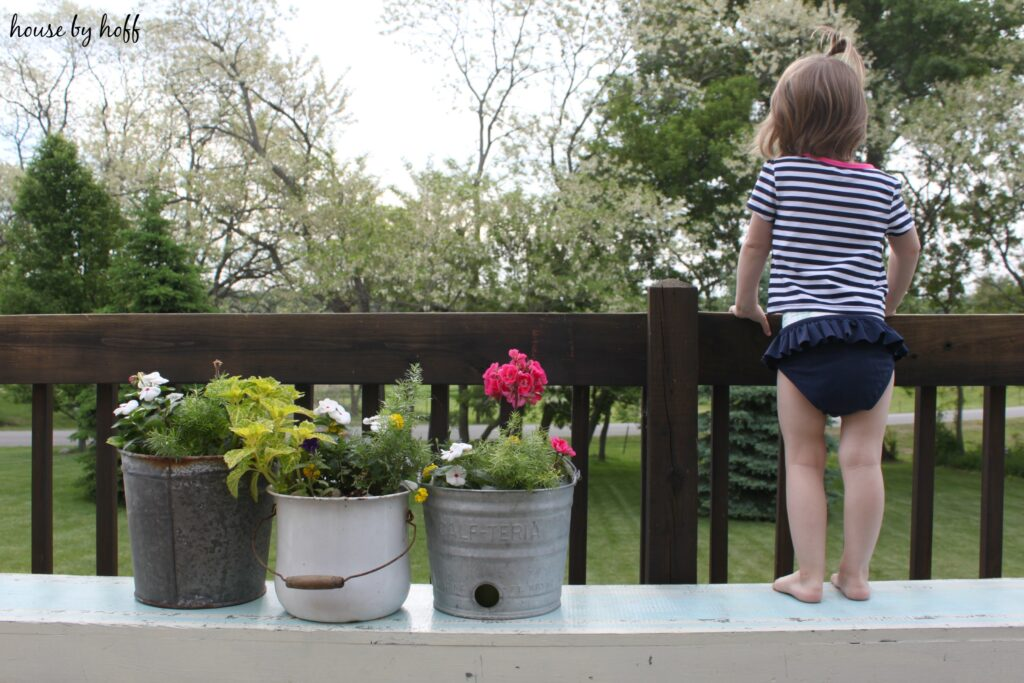Little girl standing on bench looking over a railing.