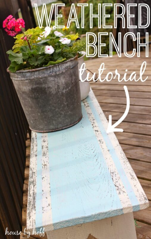 Weathered bench with pot of flowers on it.