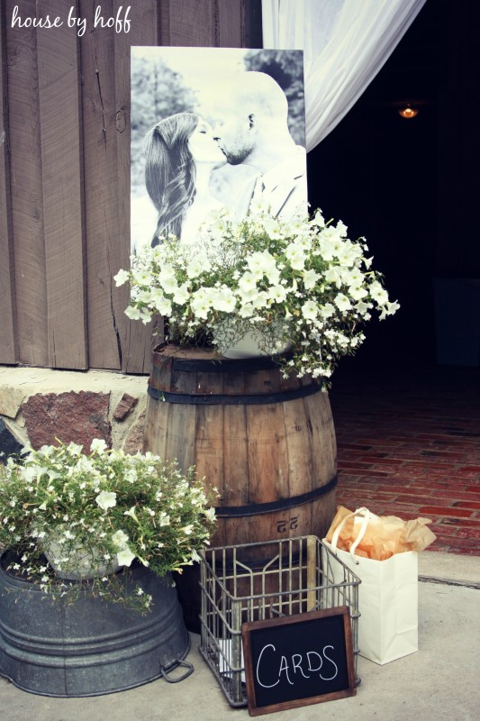 Wooden Barrel with flowers and a picture of the couple kissing behind it.
