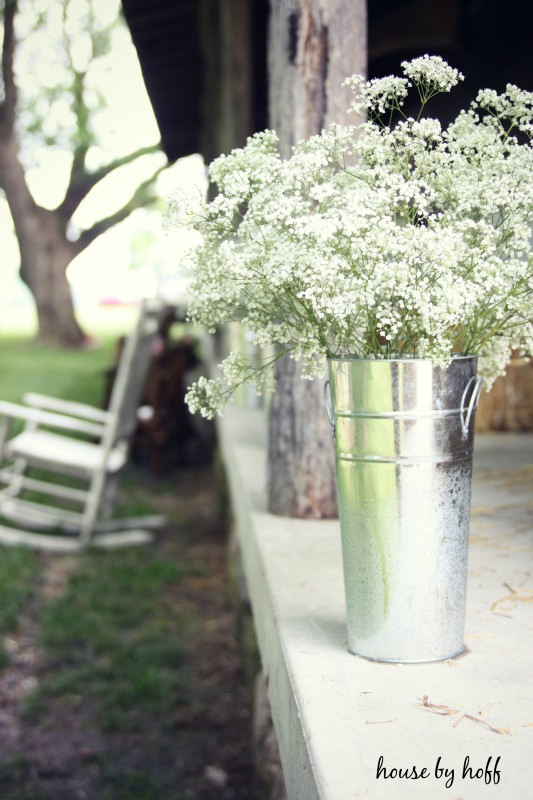 Galvanized steel containers with flowers in them on table.