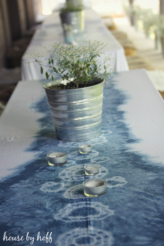 Tie dyed table cloth in soft blue and white with plant on table.