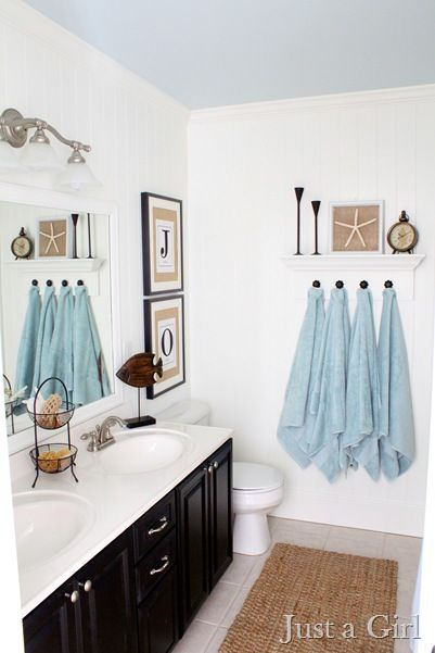Small bathroom with blue towels and seashell picture on the wall.