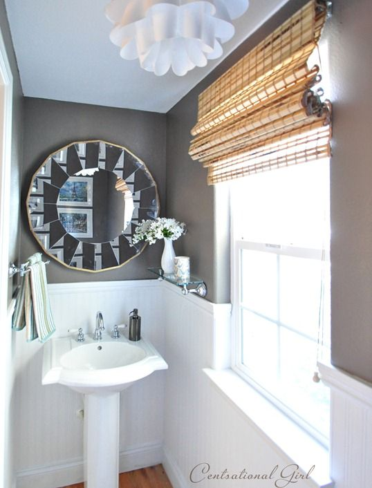 Ballard mirror on wall in bathroom and stand alone sink.
