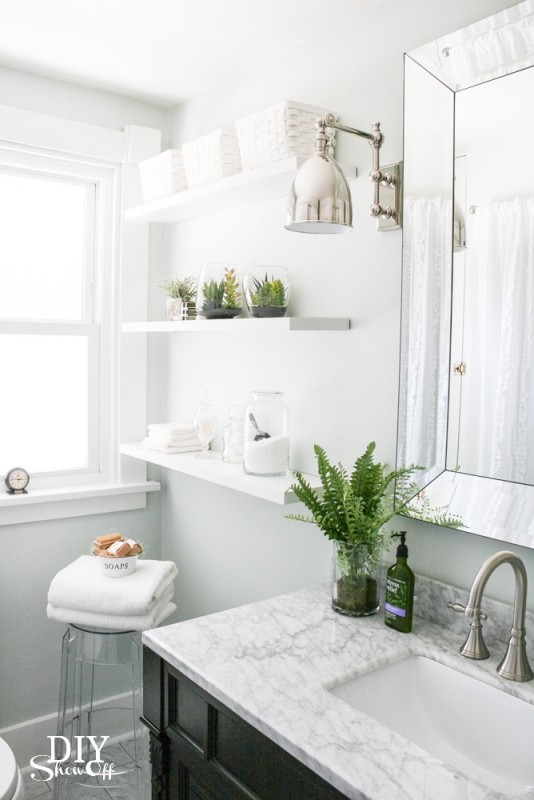 All white bathroom with green plants and chrome lights.